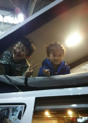 子供たちがキャンピングカーのポップアップルーフではしゃいでいる写真