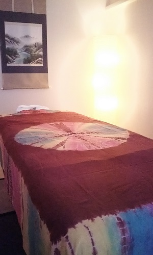 和室でエキゾチックな上掛けをマッサージベッドに使っている画像