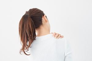 身体の歪みからくる肩こりを気にする女性の画像